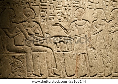 Egyptian hieroglyphs and human figures engraved on stone