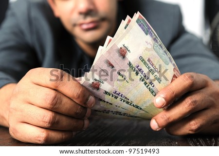 Egyptian man counting money in Egyptian currency - stock photo