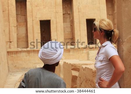 Egyptian man showing tourist woman Egyptian temple, Egypt - stock photo