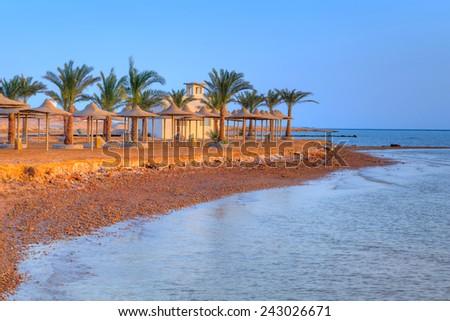 Egyptian parasols on the beach in Hurghada - stock photo
