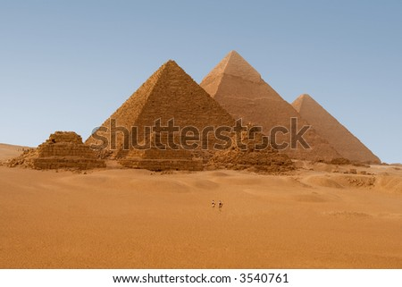 Egyptian pyramids in Giza. 2 policemen on their camels provide visual clue about how gigantic these pyramids are. - stock photo