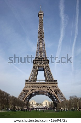 Eiffel tower and blue skies with airplane exhaust stripes around - stock photo