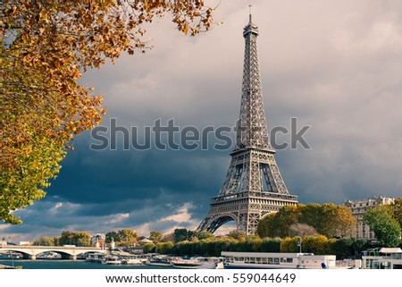 Eiffel Tower and Seine river against dramatic dark cloudy sky in autumn. Paris, France. Filtered image.
