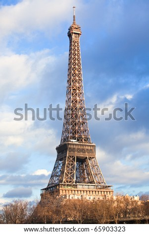 Eiffel Tower at December on cloud sky background. vertical shot - stock photo