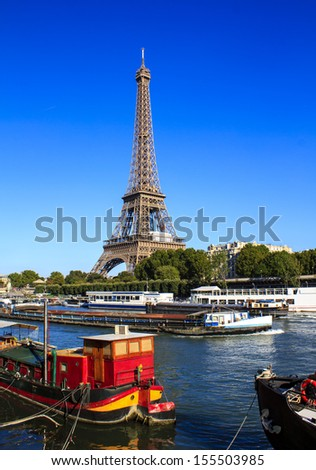 Eiffel Tower in Paris - view from the Seine river bank with stationary and moving boats.  - stock photo