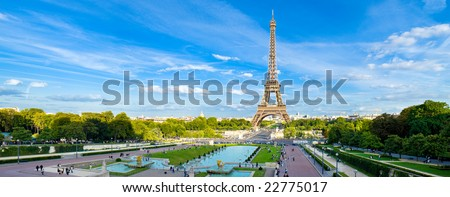 Eiffel Tower panorama, with cloudy blue sky and surrounding park. - stock photo