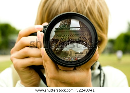 Eiffel tower reflection in camera lens with blurred woman face - stock photo