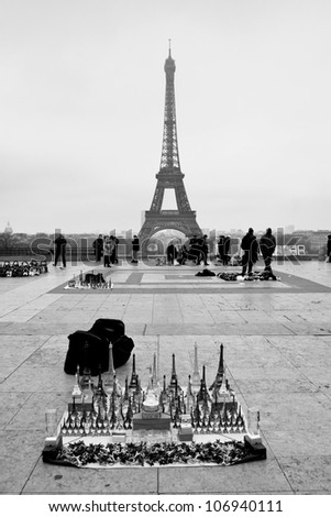 Eiffel Tower Souvenirs with the tower in background, classic black and white view - stock photo