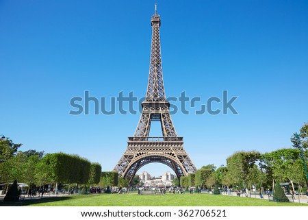 Eiffel tower, sunny summer day with blue sky and green Field of Mars in Paris - stock photo