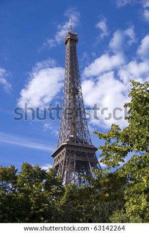 Eiffel tower view among trees - stock photo