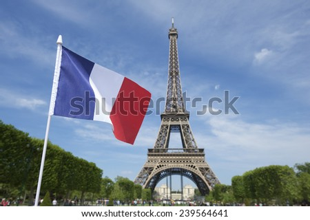 Eiffel Tower with French flag flying in bright summer sky - stock photo