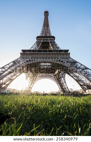 Eiffel Tower with sun rise and green grass with blur and flare booked effect  - stock photo