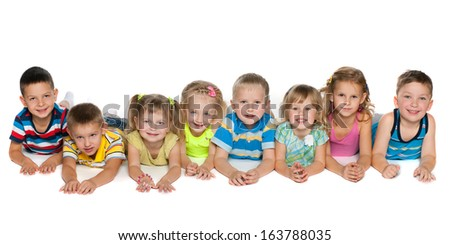 Eight children are lying on the floor on a white background
