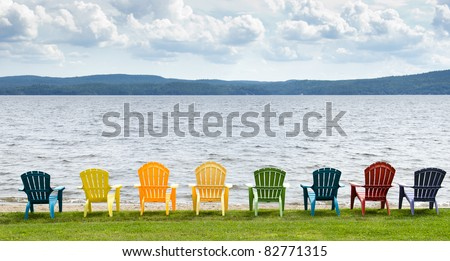 Eight colorful Adirondack chairs lined up on the beach looking out on the lake, mountains and clouds. - stock photo