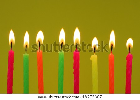 eight colorful birthday candles with green background - stock photo