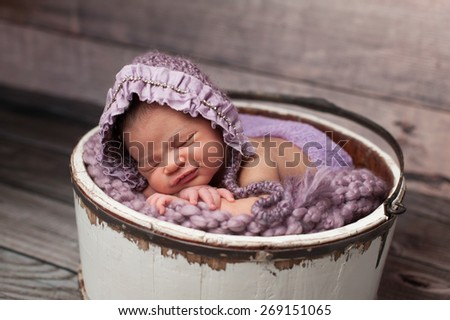 Eight day old newborn baby girl sleeping in a vintage, white wooden bucket. She is wearing a lilac colored knitted bonnet. - stock photo