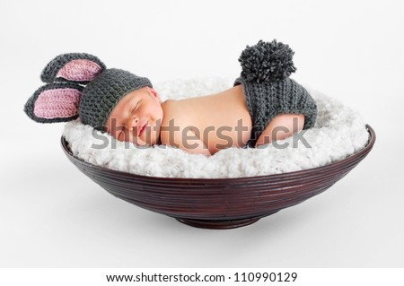 Eight day old smiling newborn baby boy wearing bunny ears and tail. He is sleeping on his stomach in a basket. Shot in the studio on an isolated white background. - stock photo