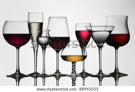 Eight difference glasses of wine and spirit, on a mirror and white background. - stock photo