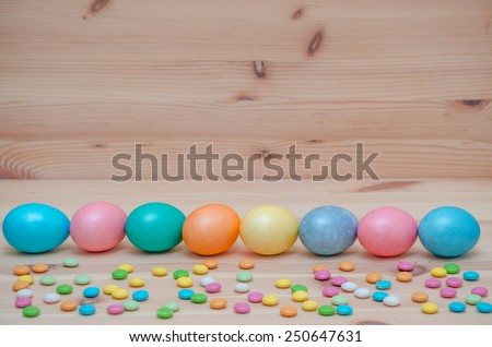 eight easter eggs pastel colored with candle on the vintage wooden background - stock photo