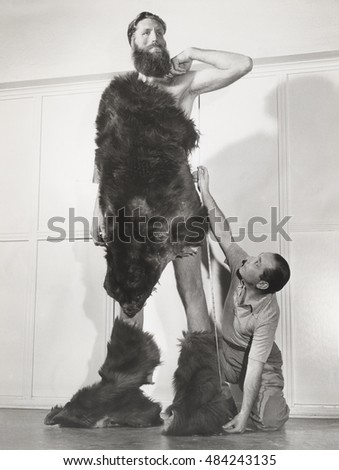 Eight foot man measured for custom tailored fur suit