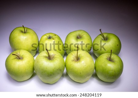 Eight green apples painted with light - stock photo