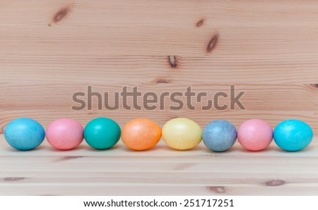 eight happy easter eggs pastel colored on the vintage wooden background - stock photo