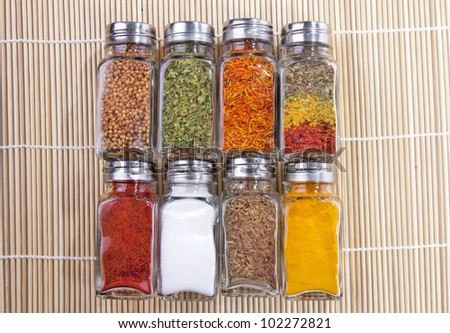 Eight jars of spices on the wooden background - stock photo
