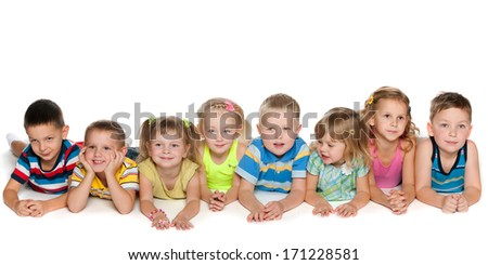 Eight joyful children are lying on the floor on a white background