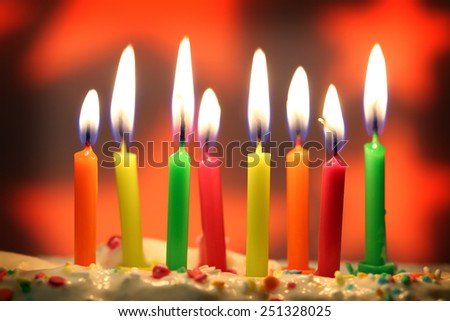 eight lit birthday candles close up, shallow dof - stock photo