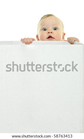 eight month baby holds on to the white box - stock photo