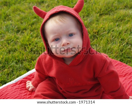 Eight month old child in a devil costume.