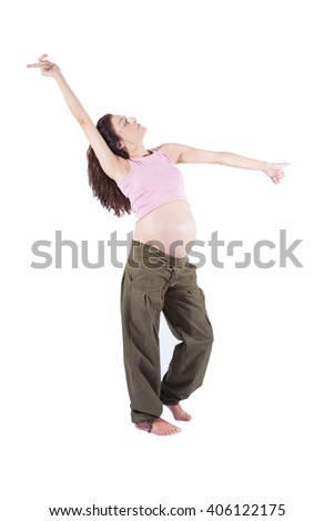 eight month pregnant brunette brown hair woman naked paunch pink shirt green trousers standing and dancing isolated over white background