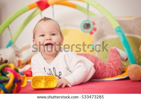Eight months old baby girl playing with colorful toys on a floor mat