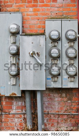 Eight old weathered rusty power meters on a orange and red brick wall - stock photo