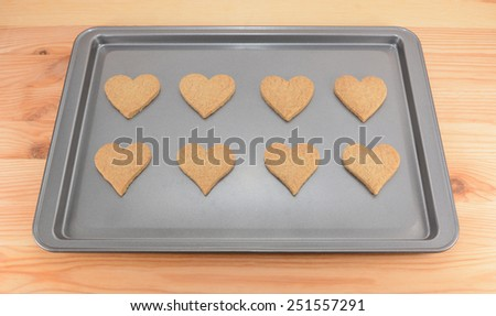 Eight plain heart-shaped biscuits on a cookie sheet, fresh from the oven - stock photo