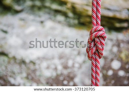 eight rope knot on rocky background - stock photo