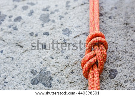 eight rope knot on rocky background