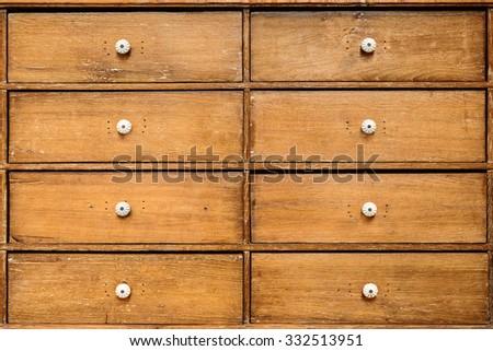 Eight vintage wooden drawers with white enamel knobs - stock photo