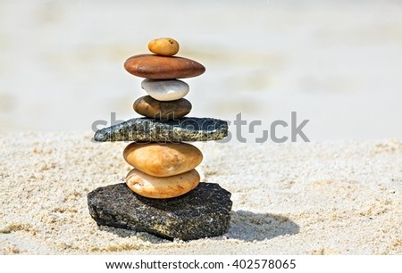 Eight white and brown stones are on sandy beach - stock photo