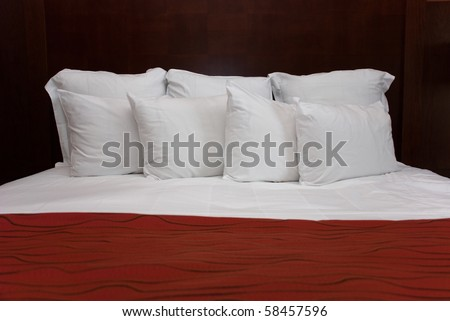 Eight white fluffy pillows on white sheets with a red bedspread against a wood headboard.
