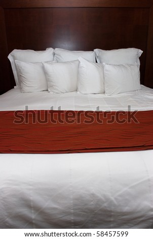 Eight white pillows on a fluffy white bed with red blanket against a wood headboard.