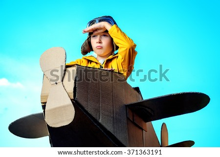 Eight-year boy playing with a cardboard airplane outdoor over sky background. Childhood. Fantasy, imagination. - stock photo