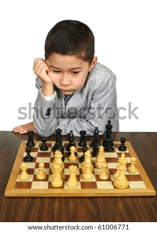Eight-year-old boy concentrating deeply on a chess move, over pure white background - stock photo