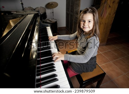Eight year old girl is happy playing the piano - stock photo