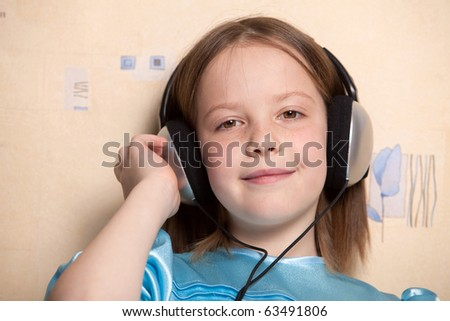 Eight year old girl listening music in headphones indoors - stock photo