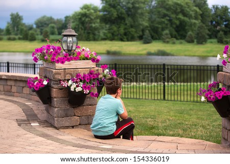 Eight years old boy enjoying his time by sitting on the steps and putting his hands on his chin - stock photo