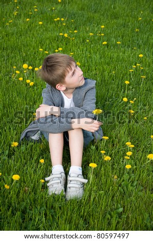 eight years old boy sitting on grass with dandelion in his hand