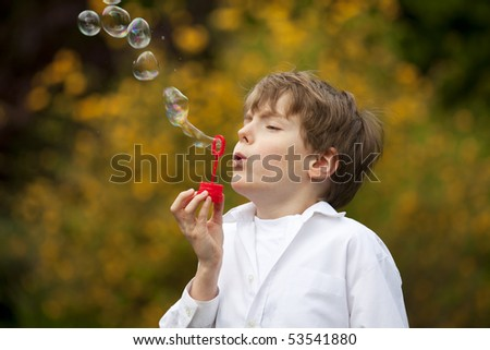 eight years old handsome boy having fun with soap bubbles