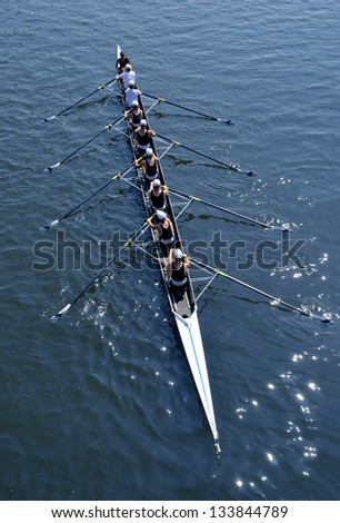 Eight young women are rowing in a skiff on a sunny day. - stock photo