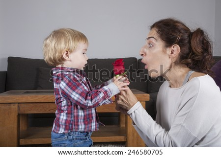 eighteen month aged blonde baby with brunette woman mother gift rose flower indoor - stock photo